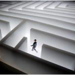 Man walking in bright white maze