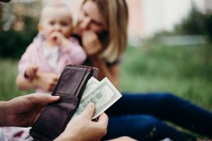 man getting money out of wallet with child and woman in the background