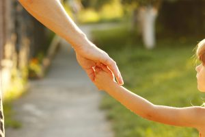 Child and parent holding hands outside